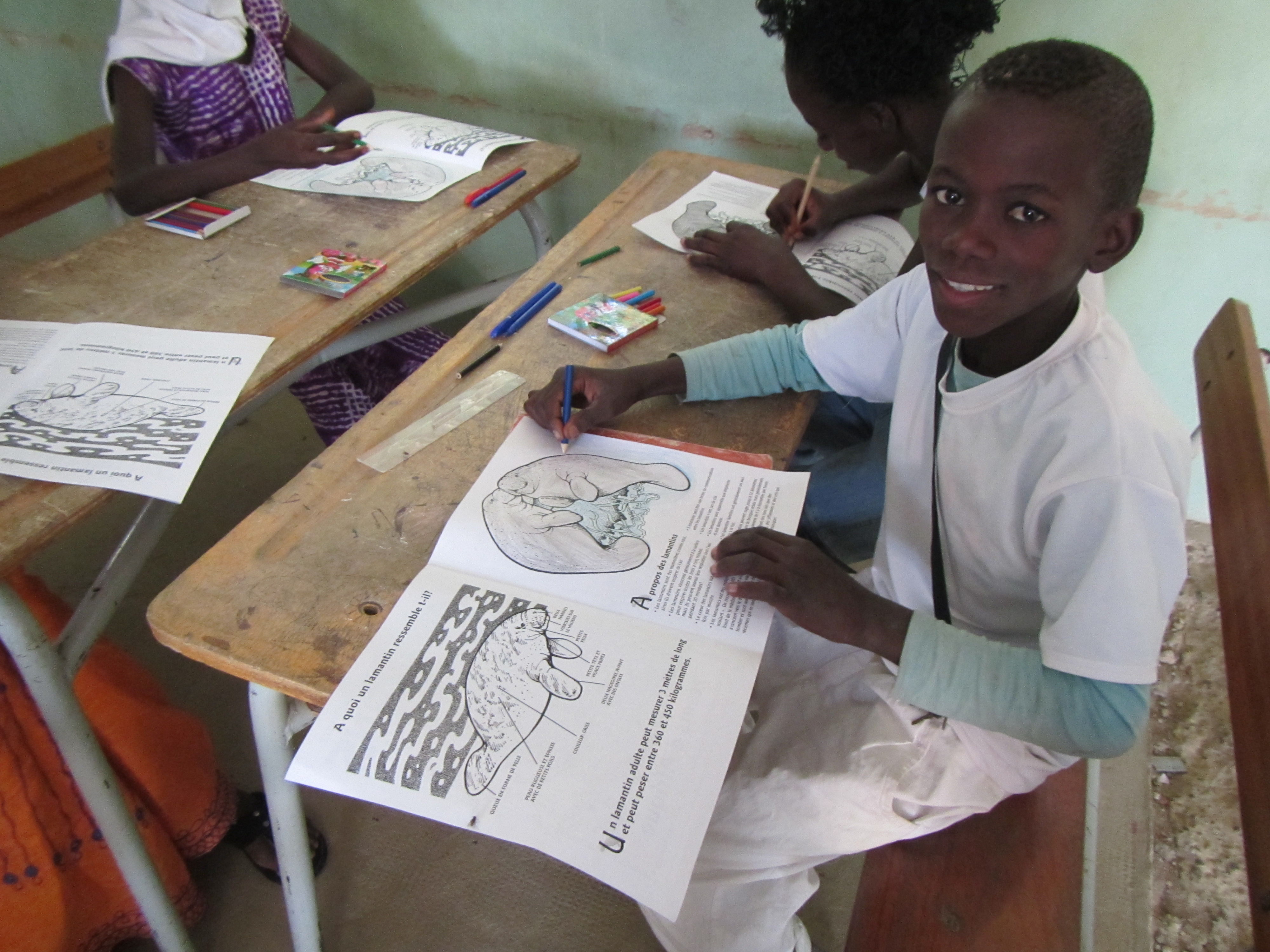 A young boy with a manatee coloring book during an educational program in Senegal.