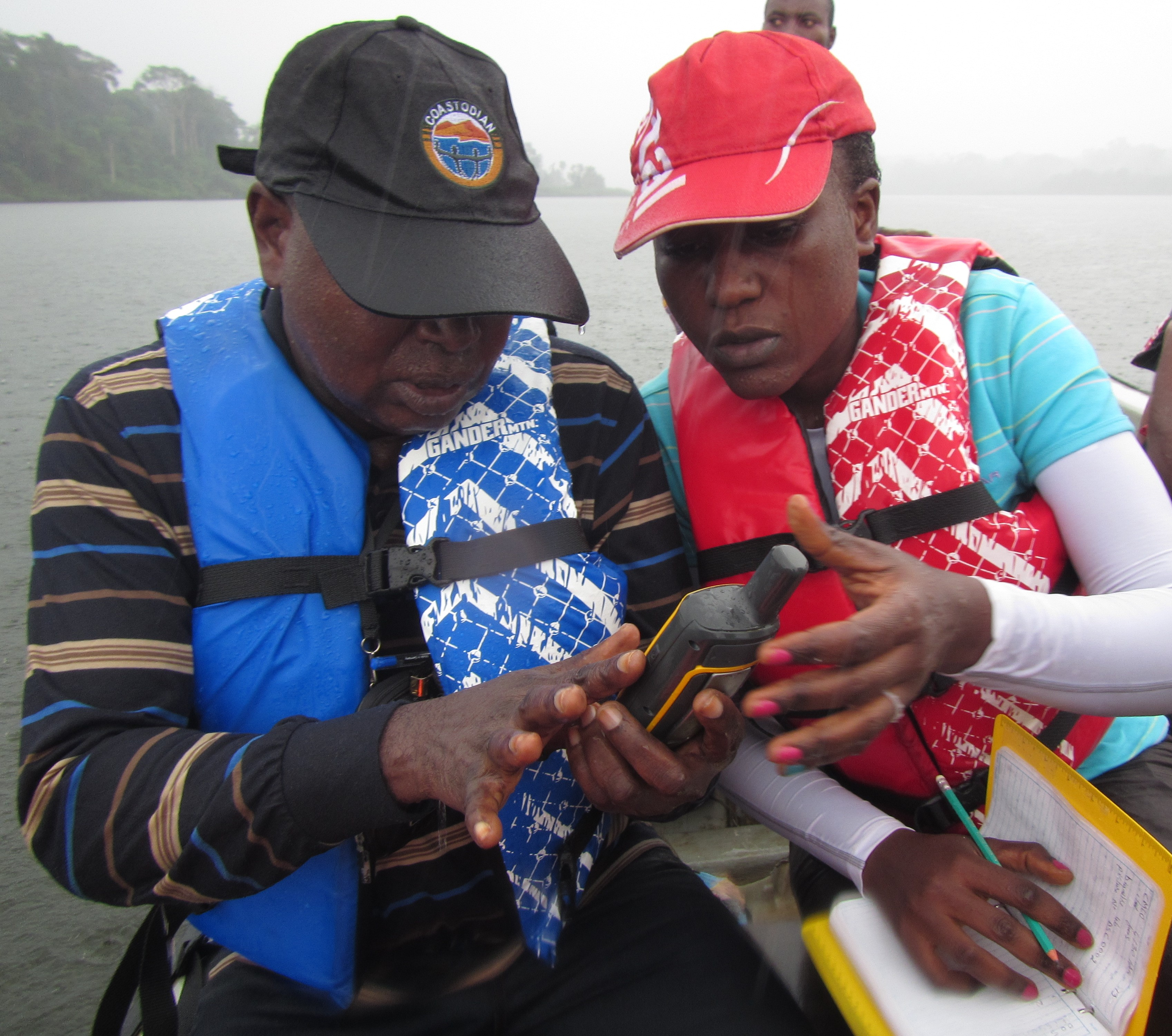 Trainees from Democratic Republic of the Congo and Cameroon read a GPS in a downpour during field work.