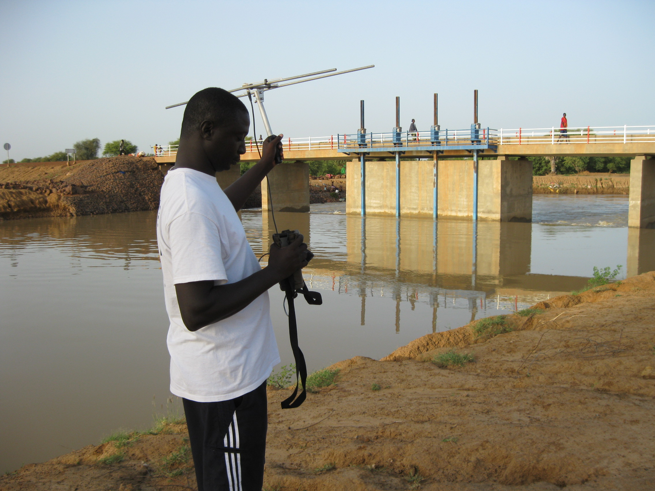 Tomas Diagne listens for a signal from a satellite tagged manatee near the Navel dam, in eastern Senegal, where it was rescued.